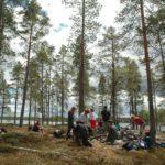Norwegen -Seminarteilnehmer im Wad auf einer Insel. Bereiten das Lager.