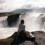 Island - Frau sitzt am Godhafoss