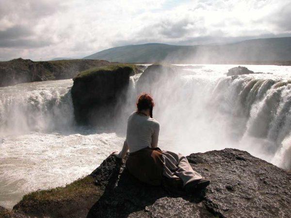 Schamanische Reise, Wasserfall als Begleitung. Island - Frau sitzt am Godhafoss