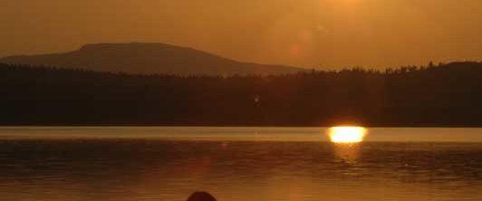 Norwegen -Blick gegen die untergehende Sonne, auf Mann im Schneidersitz am Seeufer