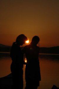 Vereinsstatuten -Blick gegen die untergehende Sonne, auf zwei Frauen im Gespräch am Seeufer
