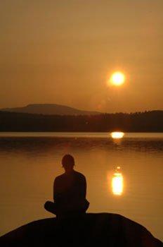 Orte der Kraft - Mann sitzt am See, bei Sonnenuntergang