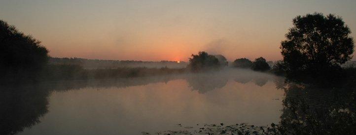 Fluss im Morgennebel bei Sonnenaufgang