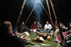Menschen sitzen um ein Feuer im Zelt