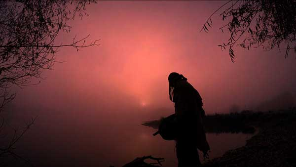 Fylgja -Krafttiertanz - Video - Olaf Bernhardt_Mann in Schamanengewand bei Sonnenaufgang an einem See