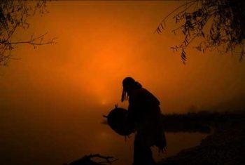 Schamane mit Trommel an einem See, bei Sonnenaufgang