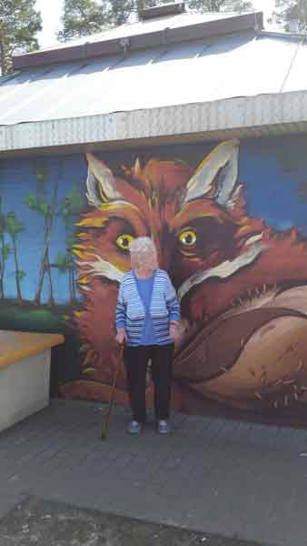 Bild der Oma vor einem Wand-Gemälde eines Fuchses