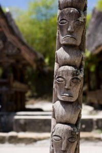 Mit Gesichtern beschnitzter Pfahl _ Symbol für Seminar Anhenkraft