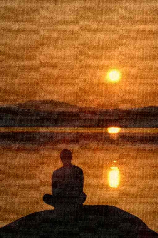 Person sitzt auf Stein am See bei Sonnenuntergang