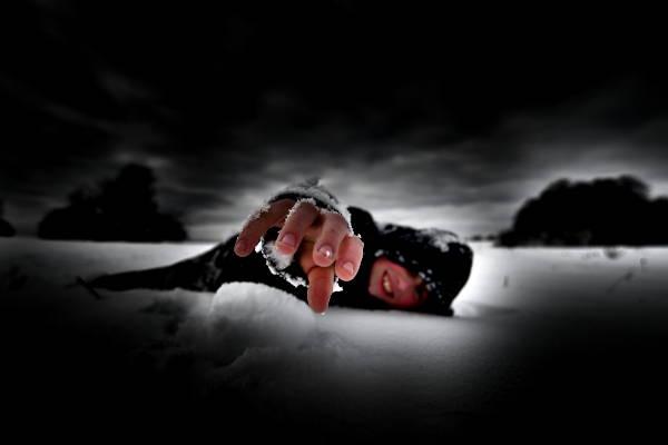 Mensch in einer Notsituation, liegend im Schnee - eine Hand austreckend
