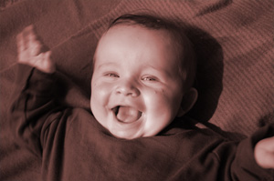 Freude und Dankbarkeit - Baby liegt auf dem Rücken und lacht