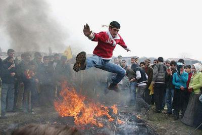 Frühlingserwachen - Im Kreise vieler Zuschauer spingt ein Mann über ein Feuer