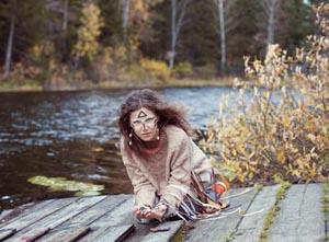 Geister rufen - Junge Frau mit bemahltem Gesicht macht ein Ritual auf einem Bootssteg