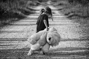 sinnkriese - Kind läuft, mit Stofflöwen unterm Arm, alleine einen Feldweg entlang